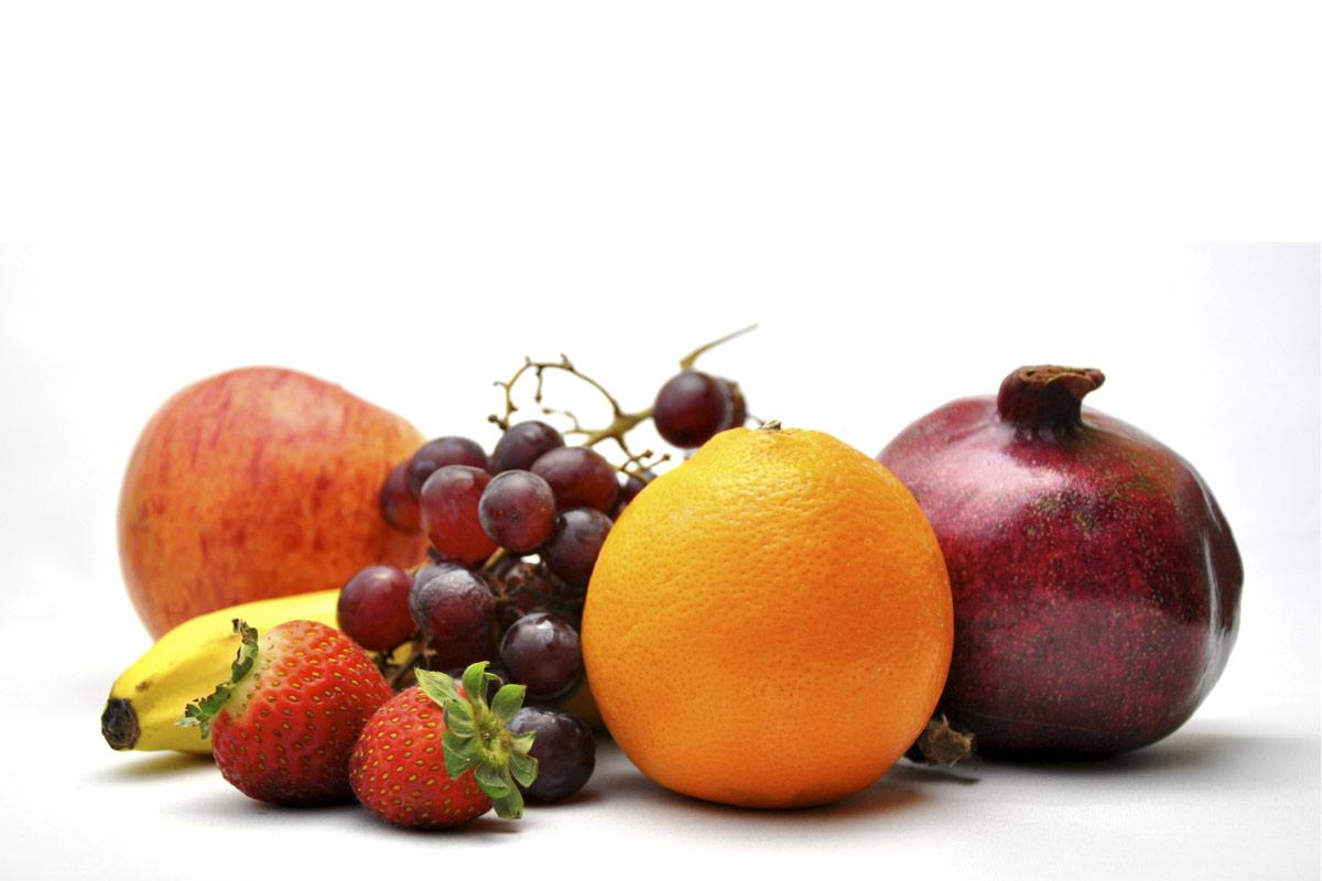 Apfel, Orange, Banane, Erdbeeren, Weintrauben, Granatapfel vor weißem Hintergrund