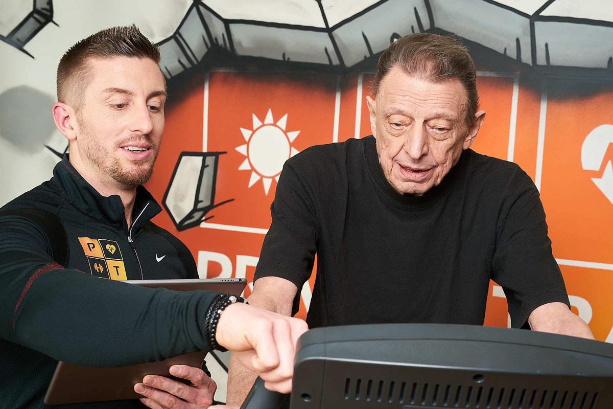 Personal Trainer Daniel Schlerith mit einem älteren Kunden am Ergometer