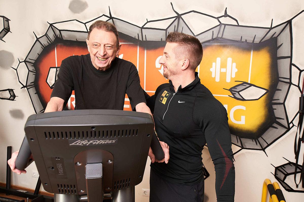 Personal Trainer Daniel Schlerith mit einem älteren Herrn beim Training am Ergometer