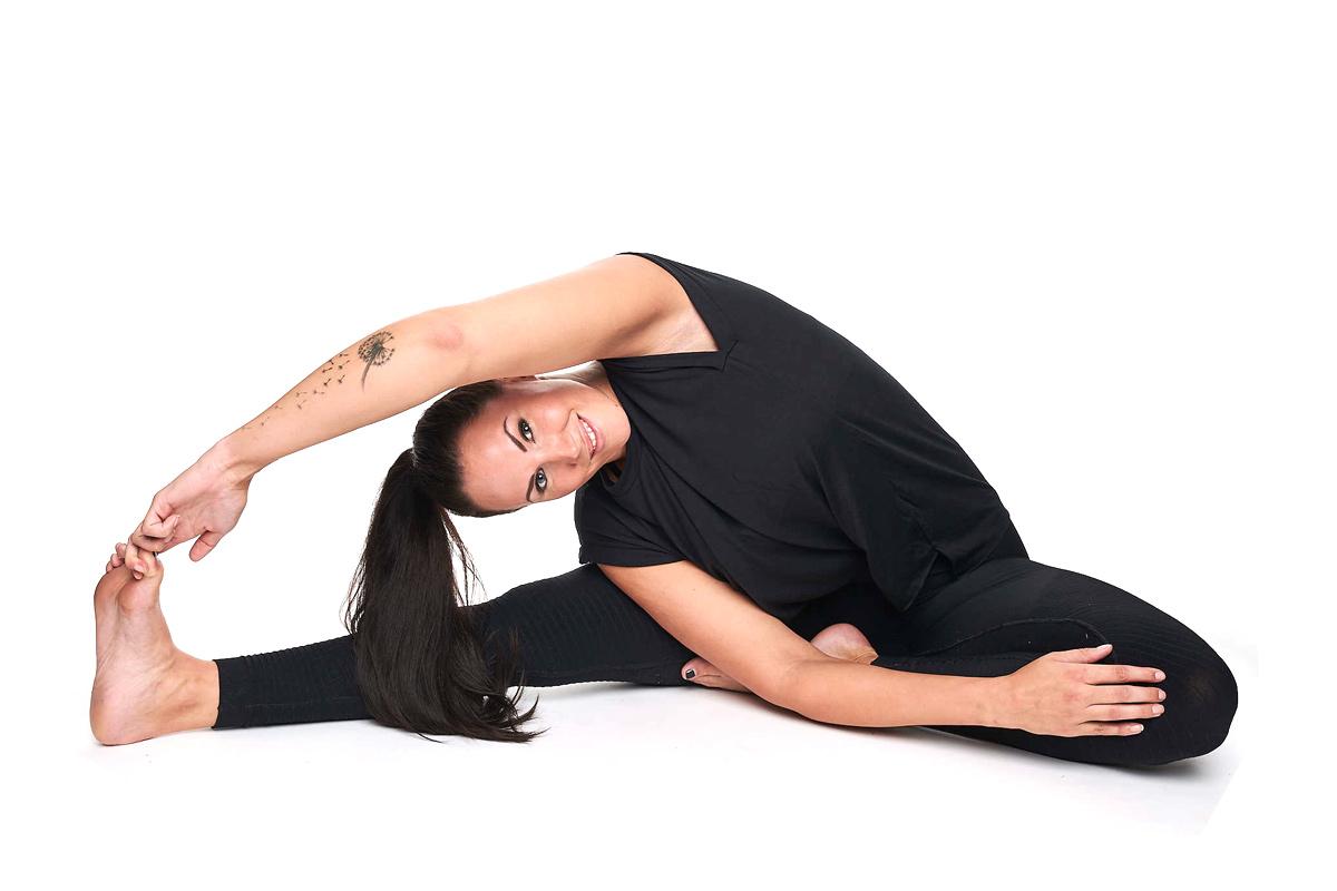 Personal Trainerin Jasmin Prucha bei der Yoga Position gedrehter Kopf zu Knie